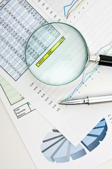 Pen, vergrootglas en het werkdocument met een diagram