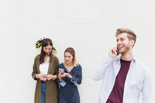 Pendelaars die mobiele telefoon voor muur met behulp van