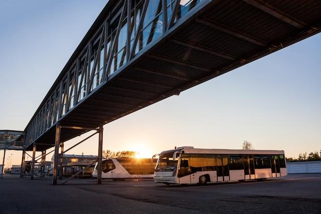 Pendelbussen op de parkeerplaats van de luchthaven bij de jetway in de stralen van de ondergaande zon