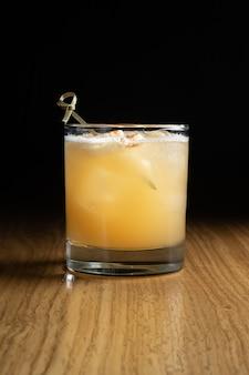 Penicilline - een op whisky gebaseerde alcoholische cocktail met citroensap en honing-gembersiroop in een transparant glas op een houten tafel