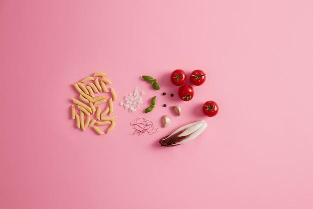Penne droge rijstpasta basilicum, witlofsalade, tomaten, knoflook rode chilipeperdraden voor het bereiden van heerlijke italiaanse gastronomische gerechten. ongekookte macaroni en ingrediënten op rooskleurige achtergrond. gezond eten