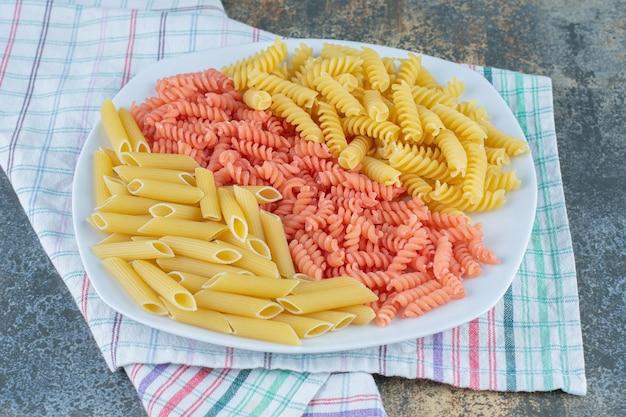 Penne en fusilli pasta in kom op handdoek, op de marmeren achtergrond.