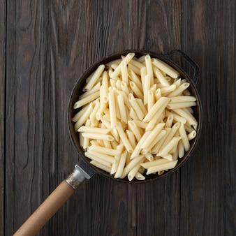 Penne italiaanse pasta in een koekenpan, rustieke stijl