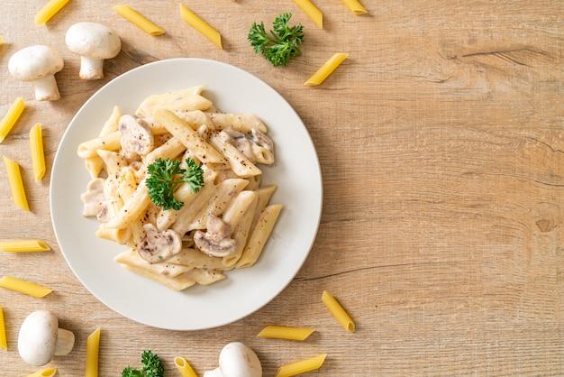 Penne pasta carbonara roomsaus met champignons - italiaanse keukenstijl