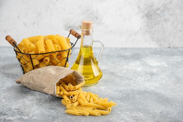 Penne pasta in een metalen container met olijfolie op grijs marmeren tafel.
