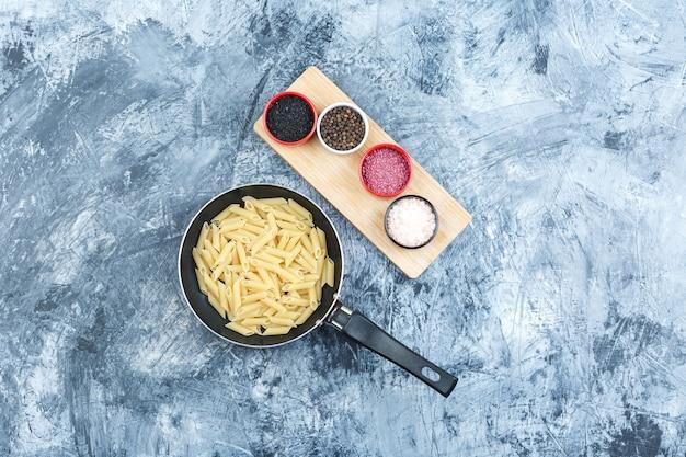 Penne pasta in een pan met kruiden bovenaanzicht op grijze gips en houten stuk achtergrond