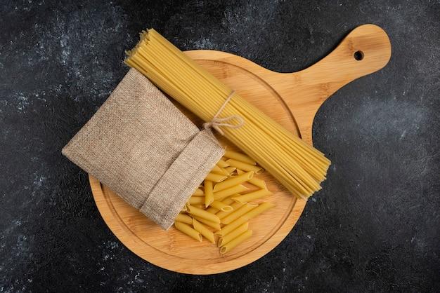 Penne pasta in een rustieke mand met spaghetties op een houten schotel.