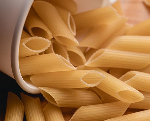 Penne pasta in macro foto vooraanzicht met witte maatbeker in compositie