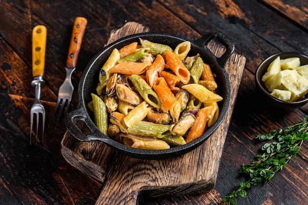 Penne pasta in roomsaus met zeevruchten. donkere houten achtergrond. bovenaanzicht.