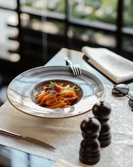 Penne pasta in tomatensaus en schaken pionnen rond.