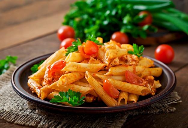 Penne pasta in tomatensaus met kip en tomaten op een houten tafel