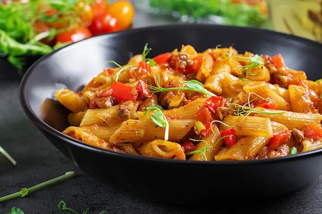 Penne pasta in tomatensaus met vlees, tomaten versierd met erwt spruiten op een donkere tafel.