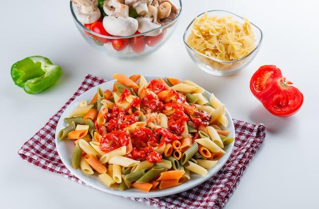 Penne pasta met champignons, tomaat, saus, peper, rauwe pasta in een plaat
