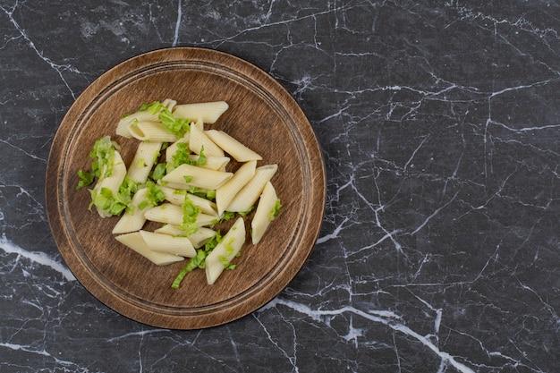 Penne pasta met groentesaus op een houten bord.