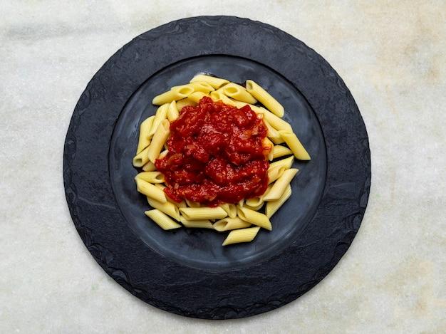 Penne pasta met in rode saus op een stenen plaat, steen of betonnen ondergrond. bovenaanzicht