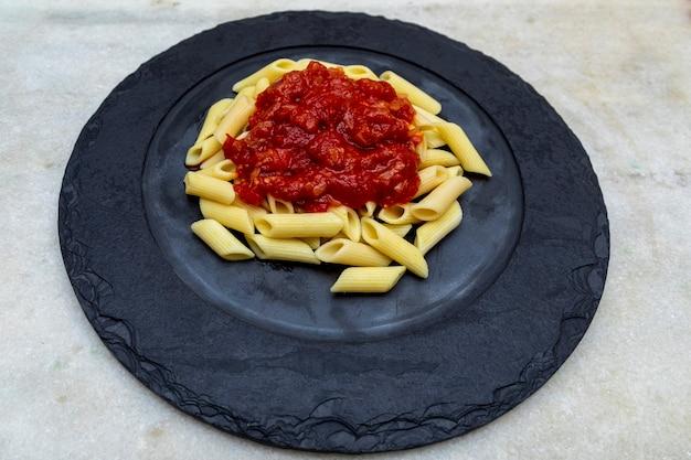 Penne pasta met in rode saus op een stenen plaat, steen of betonnen ondergrond