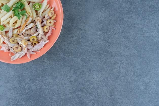 Penne pasta met kip op oranje bord.