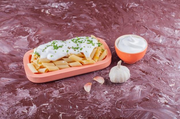 Penne pasta met mayonaise en teentjes knoflook op een lichte tafel.