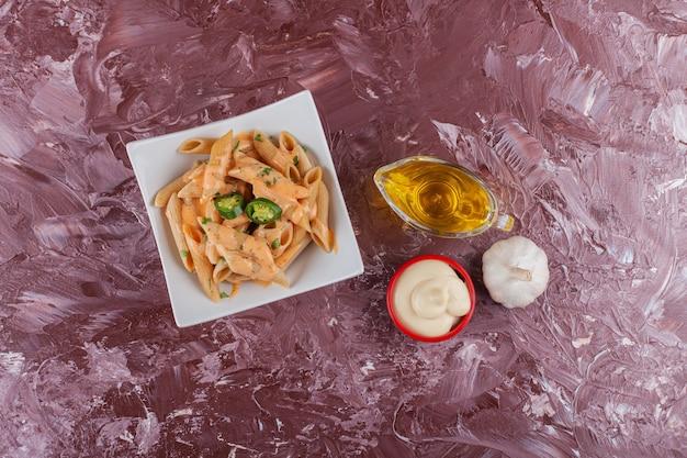 Penne pasta met mayonaise en verse knoflook op een lichte tafel.