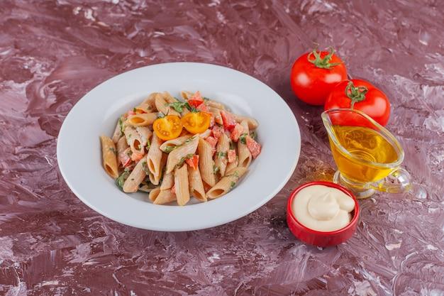 Penne pasta met mayonaise en verse rode tomaten op een lichte tafel.