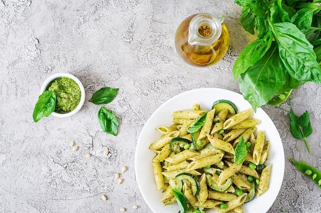 Penne pasta met pestosaus, courgette, doperwtjes en basilicum. italiaans eten. bovenaanzicht. plat liggen.
