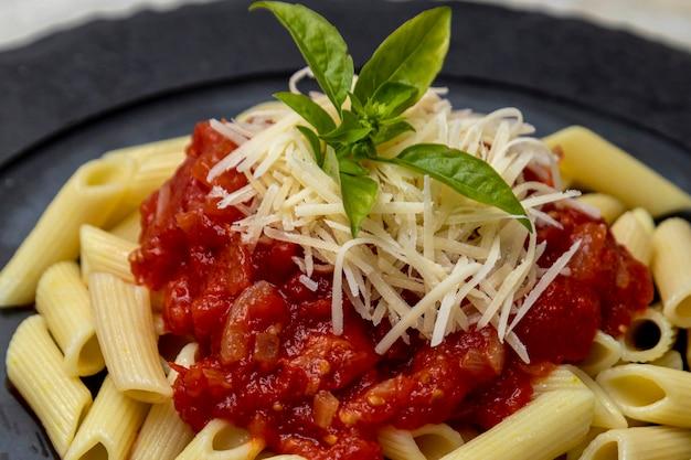 Penne pasta met rode saus en parmezaanse kaas op een zwarte plaat. steen of beton achtergrond