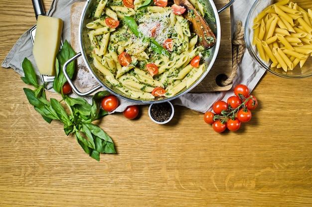 Penne pasta met spinazie, cherrytomaatjes en basilicum.