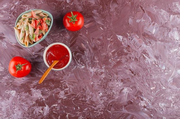 Penne pasta met tomatensaus en verse rode tomaten op een lichte tafel.