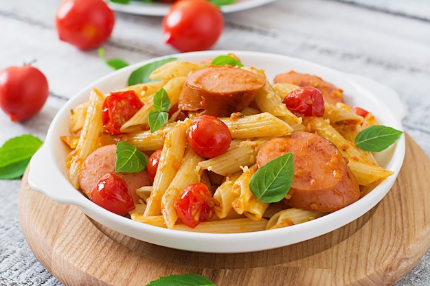 Penne pasta met tomatensaus met worst, tomaten, groene basilicum ingericht in een koekenpan op een houten tafel