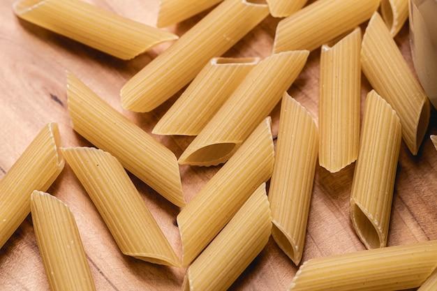 Penne pasta rauw op houten object met bovenaanzicht