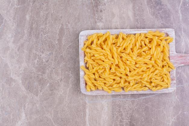 Penne pasta's op een blauwe rustieke houten schotel.