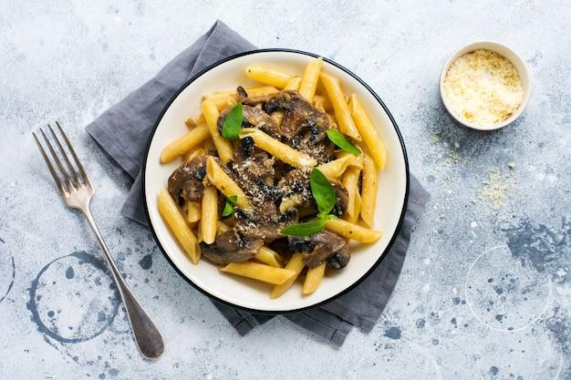 Penne rigate pasta met champignons, parmezaanse kaas en basilicum bladeren in keramische schotel op lichte oude betonnen ondergrond. selectieve focus
