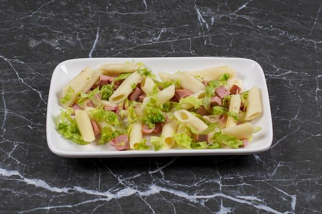 Pennedeegwaren en groentesaus op witte plaat.