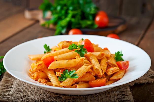Pennedeegwaren in tomatensaus met kip en tomaten op een houten lijst