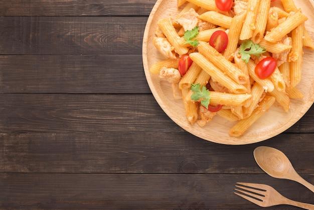 Pennedeegwaren in tomatensaus met kip op een houten achtergrond. ruimte voor tekst kopiëren