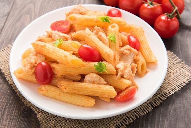 Pennedeegwaren in tomatensaus met kip op een houten lijst