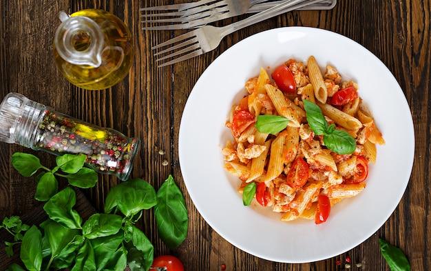 Pennedeegwaren in tomatensaus met kip, tomaten, versierd met basilicum op een houten tafel. italiaans eten. pasta bolognese. bovenaanzicht