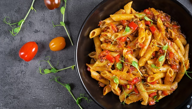 Pennedeegwaren in tomatensaus met vlees, tomaten versierd met erwtenspruiten op een donkere tafel. bovenaanzicht