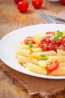 Pennedeegwaren met bolognesesaus, parmezaanse kaas en basilicum