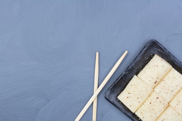 Pennedeegwaren met kruiden op een zwarte ceramische schotel