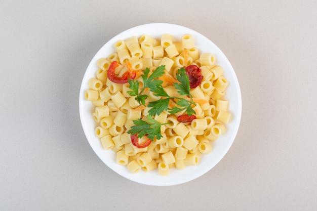 Pennedeegwaren met peterselie en tomatenplakken in witte kom
