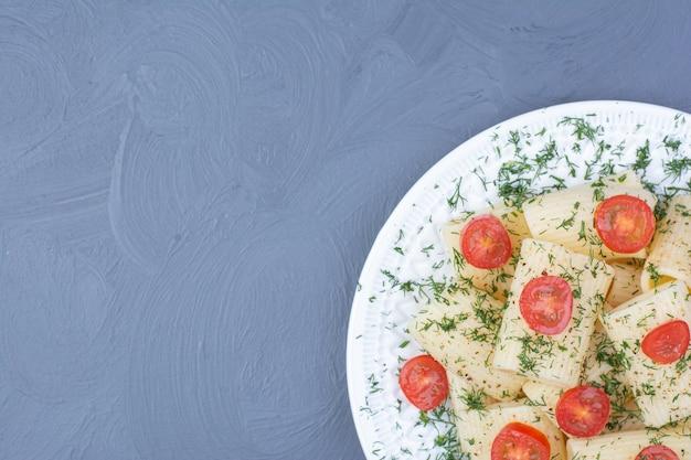 Pennedeegwaren met tomaten en kruiden in een witte plaat
