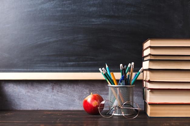 Pennen, appel, potloden, boeken en glazen op tafel, tegen de achtergrond van een schoolbord