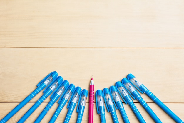 Pennen of schrijfhulpmiddelen op houten tafel en rode pen midden tussen blauwe bovenaanzicht