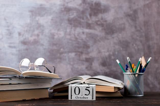 Pennen, potloden, boeken en glazen op tafel. kalender 5 oktober, kopieer ruimte.