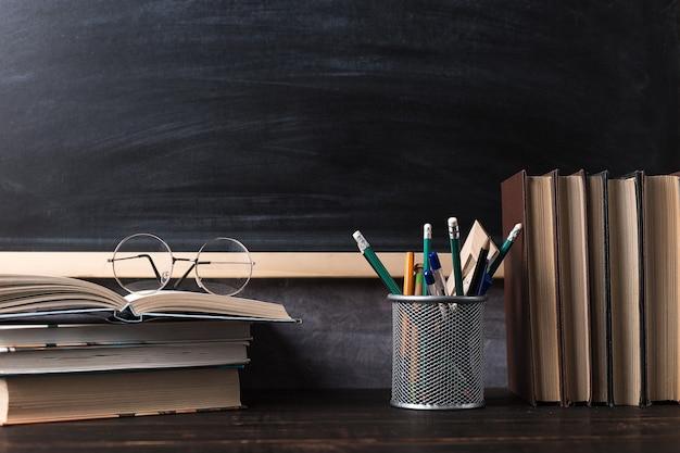 Pennen, potloden, boeken en glazen op tafel, tegen de achtergrond van schoolbord