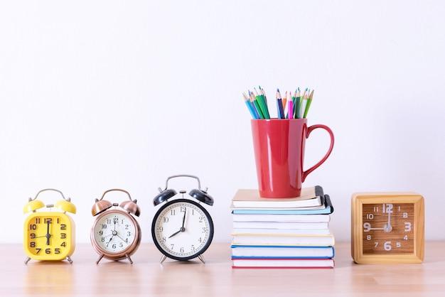 Pennenbakje op boek stapel en wekkers op houten tafel