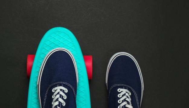 Penny board en sneakers op een zwarte achtergrond. bovenaanzicht. retro stijl