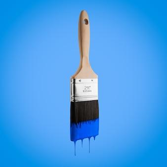 Penseel dat met blauwe kleur wordt geladen die van de varkenshaar druipt die - op blauwe achtergrond wordt geïsoleerd.