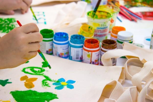 Penseel in de kinderhand die een waterkleur tekent